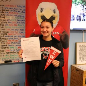 Student smiling with college acceptance letter.